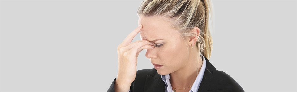 Woman placing her hand on her forehead while her head aches