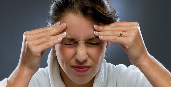 Woman putting both hands on her temples and squinting